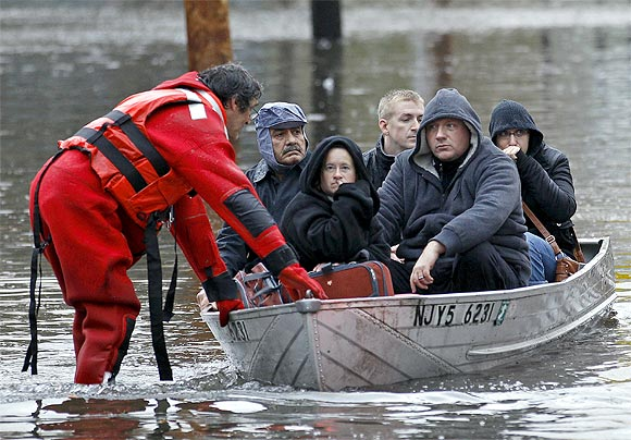 Residents are rescued by emergency personnel from flood waters brought on by Hurricane Sandy