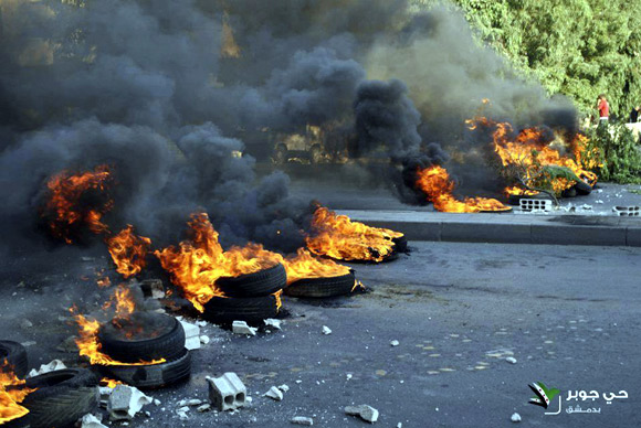 Tyres set on fire by demonstrators block a road during a protest against Syria's President Bashar al-Assad in Jubar near Damascus