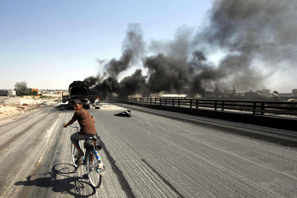 A Syrian boy rides a bicycle as smoke rises over the Syrian city of Aleppo after missiles fired from a fighter jet hit petrol tankers in the Bab al-Nayrab district