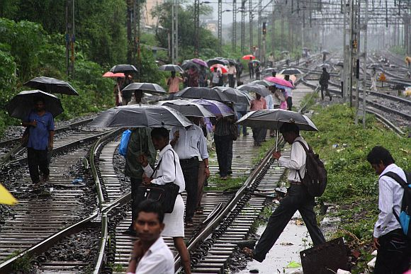 People crossing tracks in Kalyan after rains brought the trains to a halt
