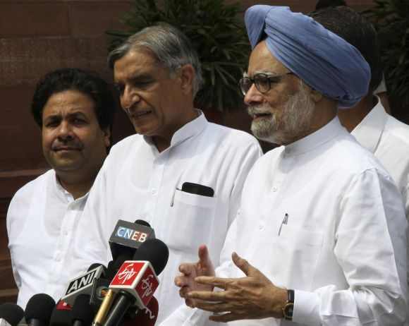 Prime Minister Singh speaks to the media as Minister of State for Parliamentary Affairs Shukla and Parliamentary Affairs Minister Bansal watch