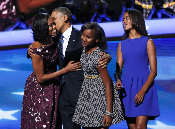 US President Barack Obama is joined on stage by First Lady Michelle Obama along with daughters Sasha and Malia