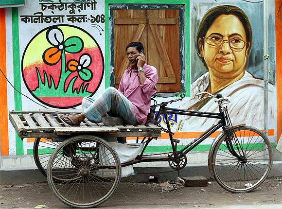 A cycle rickshaw puller speaks on a mobile phone in front of Trinamool Congress party office in Kolkata
