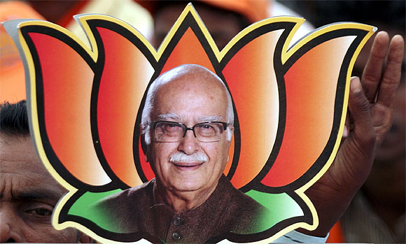 A supporter of the BJP holds a picture of BJP leader L Krishna Advani in Balasinor, Gujarat