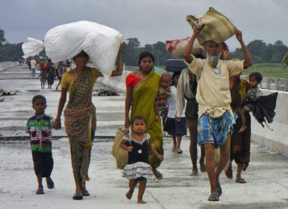Villagers with their belongings move to relief camps as they leave their locality after violence in Assam