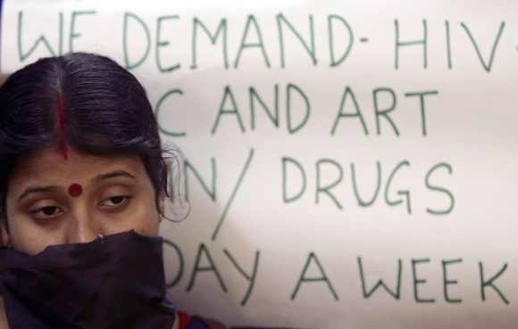 A HIV/AIDS affected Indian woman stands next to a placard during a demonstration to demand medicines for HIV-infected people