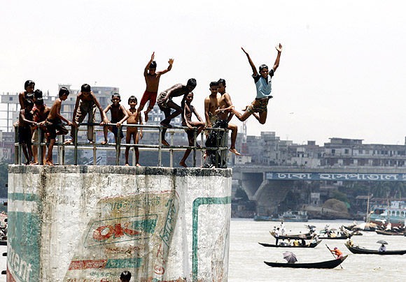 Children jump into Buriganga River to cool themselves in Dhaka