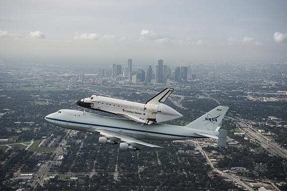 The space shuttle Endeavour, atop NASA's Shuttle Carrier Aircraft, flies over Houston, Texas