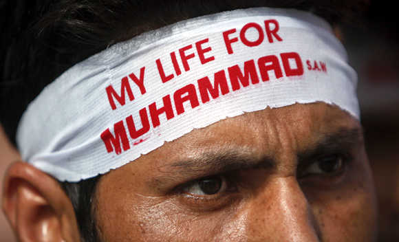 A protestor  wears a headband during a protest march towards the US consulate in Karachi