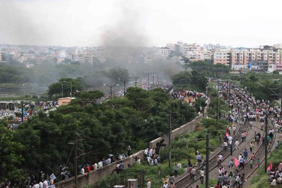 Smoke is seen as activists gather near Necklace Road in Hyderabad for a protest march