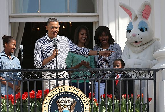 US President Barack Obama speaks while flanked by his daughters Sasha (L), Malia, first lady Michelle Obama, Robby Novak and the Easter Bunny, during the annual Easter Egg Roll on the White House tennis court April 1