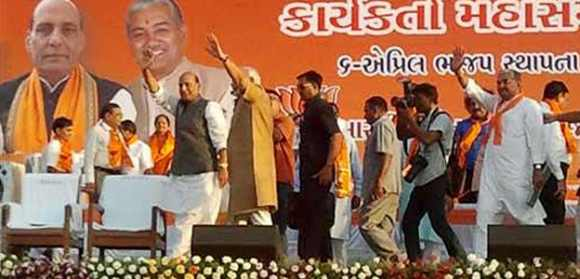 BJP chief Rajnath Singh and Gujarat CM Modi wave to supporters during the 33rd foundation day function
