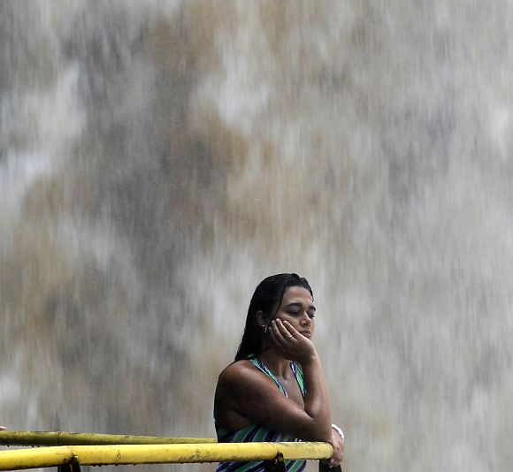 A tourist watches the Iguazu Falls from a viewing point on the border of Argentina's province of Misiones and Brazil's State of Parana