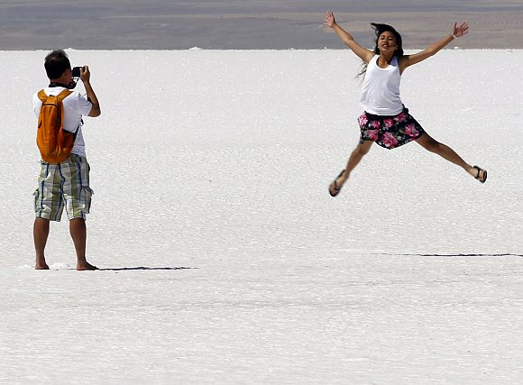A tourist poses for pictures at Tuz Golu (Salt Lake in Turkish), which is the second biggest lake in Turkey, located in the Central Anatolia Region