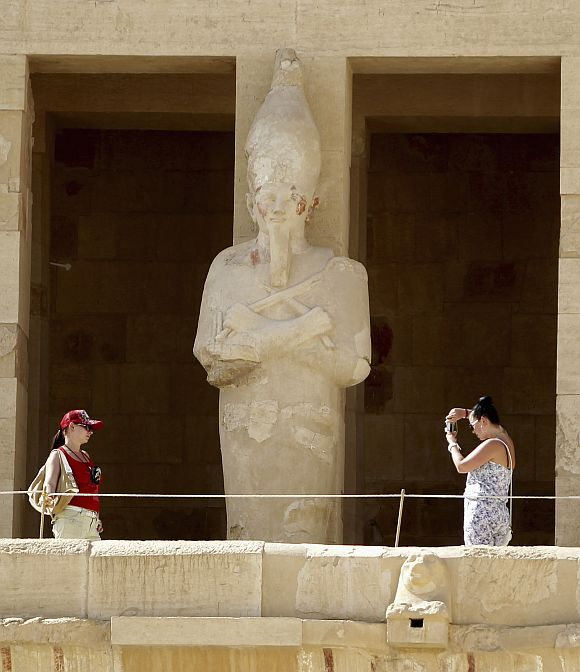 A tourist takes a photo of her sister at the Temple of Hatshepsut in Luxor