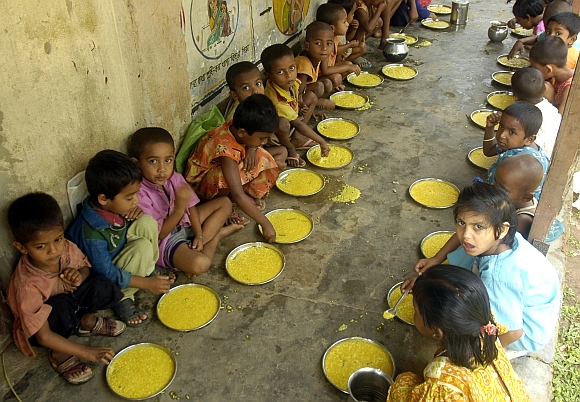 Students have a free meal distributed by a government-run school in Nalchar village, 70 km south of Agartala, Tripura
