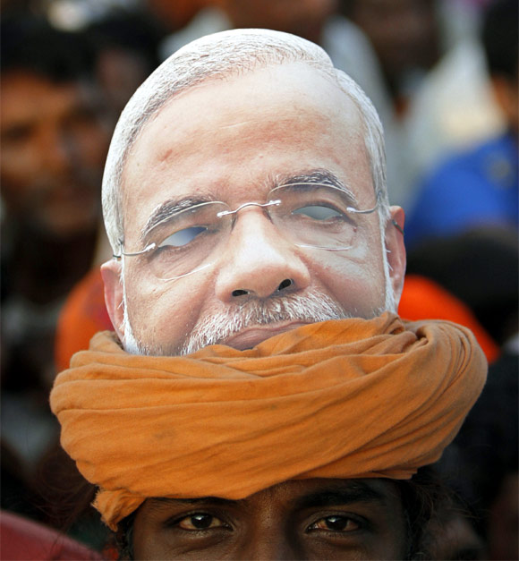 A supporter with a picture of Gujarat's Chief Minister Narendra Modi on his turban attends an election campaign rally