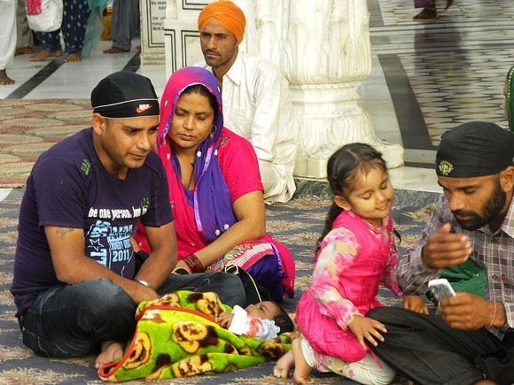 A Punjabi family relaxes in front of the Harmandir Sahib