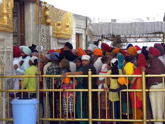 Crowds peacefully queue up, with very little jostling, early morning  to enter the Harmandir Sahib where the the holy Guru Granth Sahib is placed