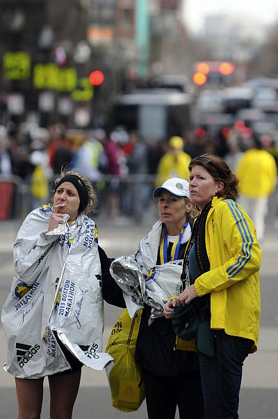 Racers and race officials look for loved ones after multiple explosions near the 117th Boston Marathon finish line