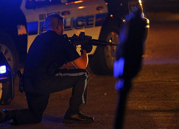 A police officer points his rifle at a man (not pictured) on the ground in Watertown
