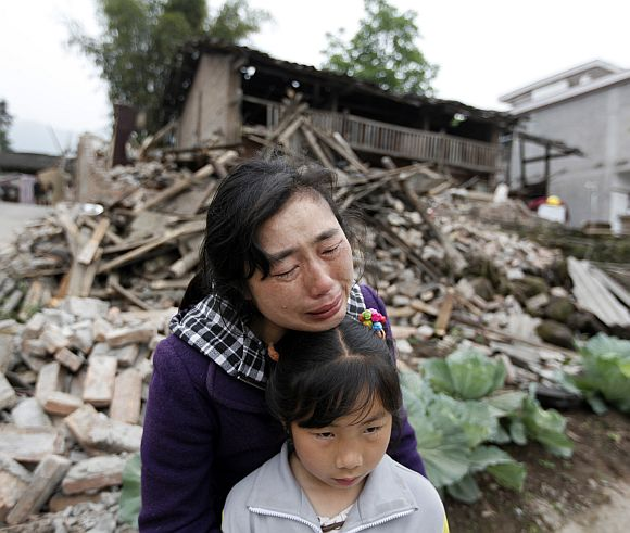 Song Zhengqiong, holding her daughter, cries in front of her damaged house