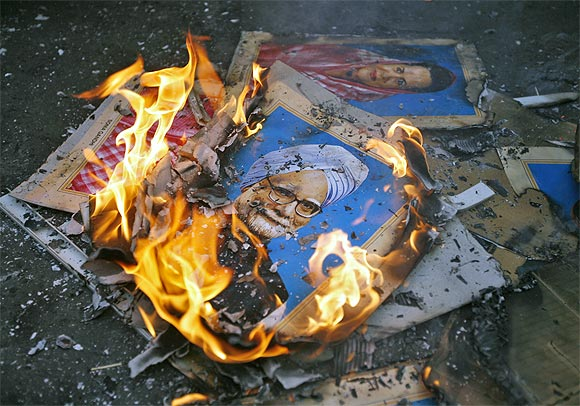 Portraits of Prime Minister Manmohan Singh and Congress President Sonia Gandhi lie in flames after they were set on fire by demonstrators during a protest