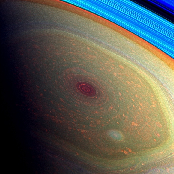 This spectacular, vertigo inducing, false-color image from NASA's Cassini mission highlights the storms at Saturn's north pole. The angry eye of a hurricane-like storm appears dark red while the fast-moving hexagonal jet stream framing it is a yellowish green. Low-lying clouds circling inside the hexagonal feature appear as muted orange color. A second, smaller vortex pops out in teal at the lower right of the image.