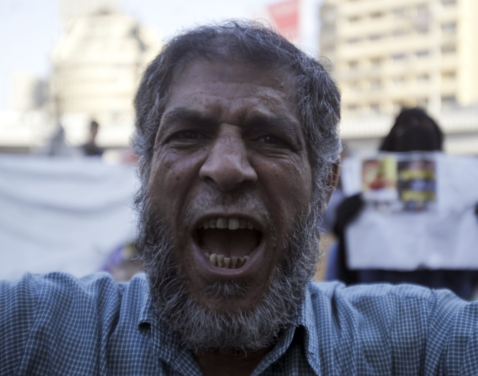 A supporter of the Muslim Brotherhood and Morsi shouts slogans against the military and interior ministry during a protest in front of Al Istkama mosque at Giza Square, south of Cairo