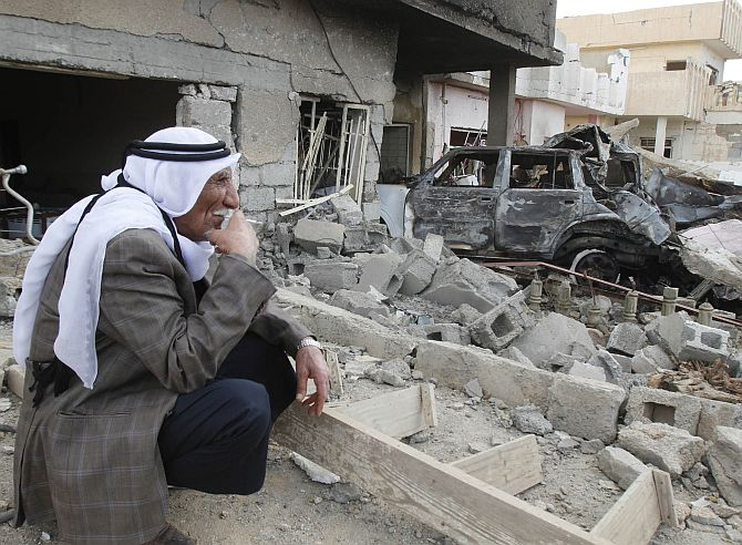 A man smokes a cigarette as he sits at the site of a bomb attack in Kirkuk