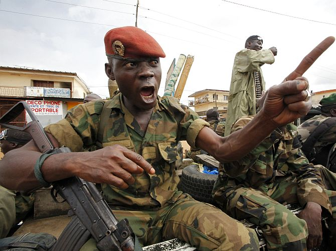 A soldier of the Ivorian Army gestures during a patrol in Dabou