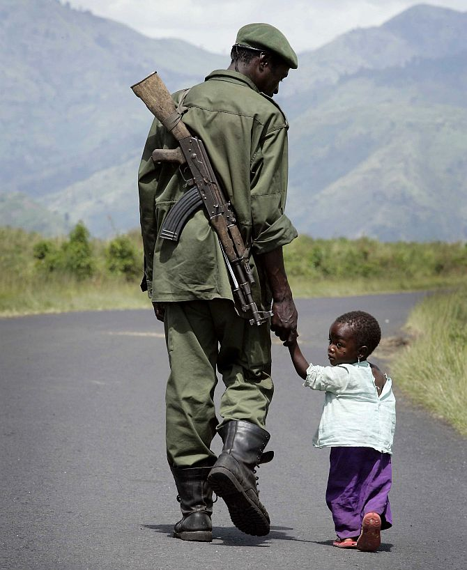 A Congolese Government soldier walks on the road towards Sake holding his daughter's hand, near the city of Goma in eastern Congo