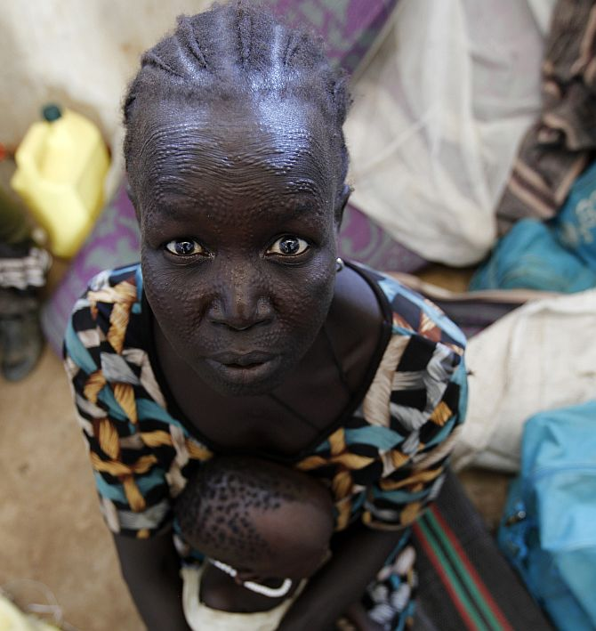 A refugee woman from Jonglei State in South Sudan sits inside a temporary shelter with her child at the registration centre in a refugee camp