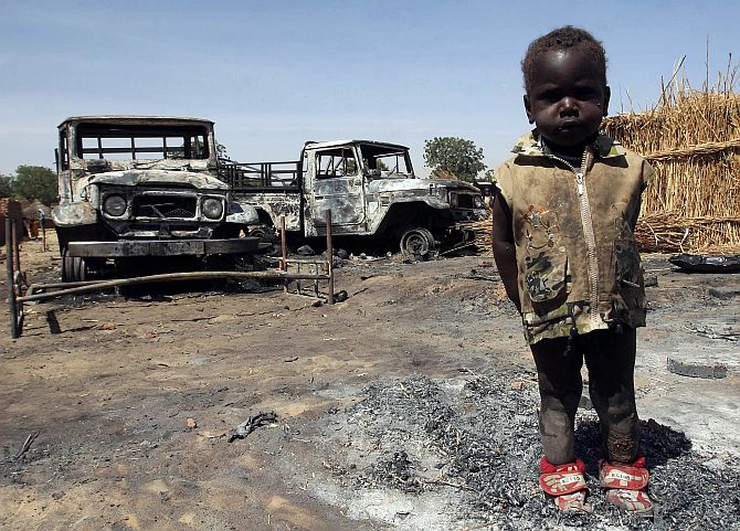 A child stands in front of cars burned during the rebels' last attack in Adre