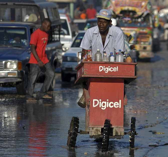 A man pushes his cart of mixed beverages through dirty water along a street in Port-au-Prince