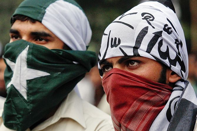 Supporters of the banned Islamic organisation Jamaat-ud-Dawa cover their faces with the Pakistan's national (left) and party flags during a protest