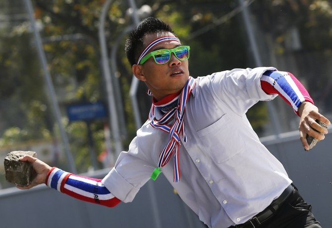 An anti-government protester wearing national colours throws a rock during clashes with police near the Government House in Bangkok