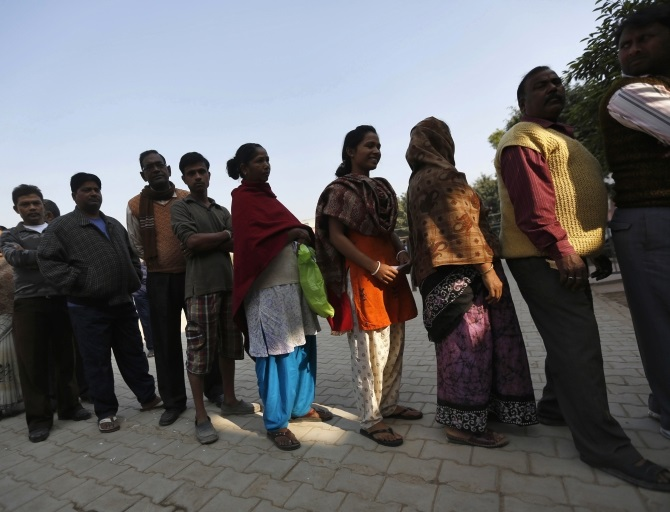 Voters line up in a queue outside a polling booth to cast their vote during the state assembly election in New Delhi