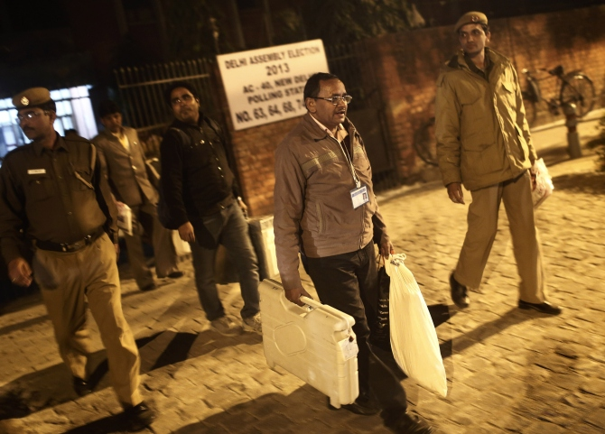 A polling officer carries electronic voting machines as he leaves a polling station at the end of polls, during the state assembly election in New Delhi.