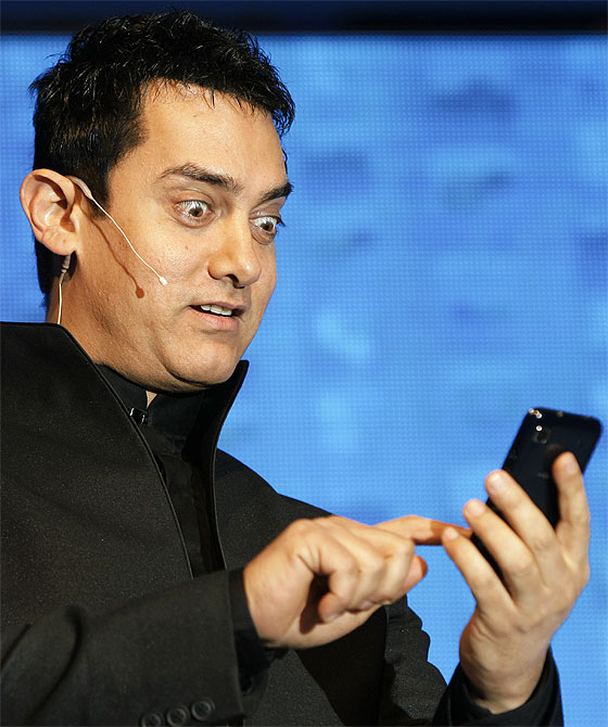 Actor Aamir Khan reacts as he holds a mobile phone during a promotional event
