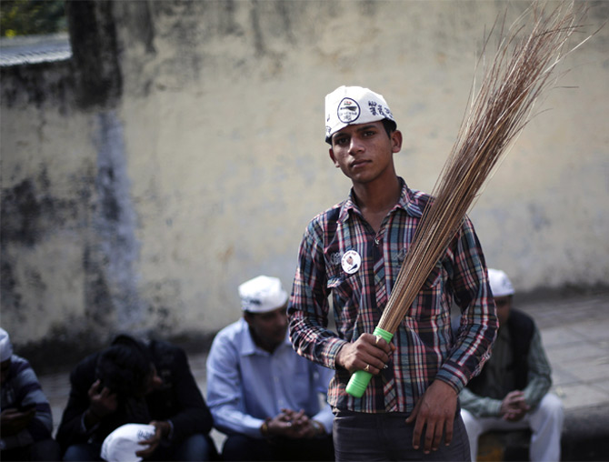 A supporter of the Aam Aadmi Party holds a broom, the party's symbol, during a rally