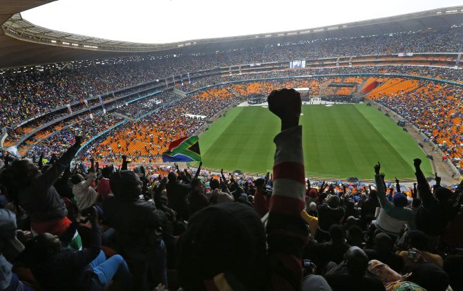 People cheer as US President Barack Obama speaks at the First National Bank (FNB) Stadium, also known as Soccer City, during the national memorial service for Nelson Mandela in Johannesburg