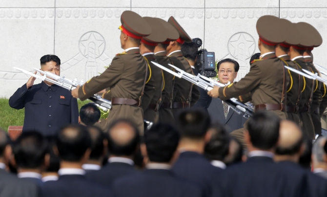 North Korean leader Kim Jong-un salutes to the members of the honour guards as he and Jang attend a commemoration event at the Cemetery of Fallen Fighters of the Korean People's Army in Pyongyang in this photograph taken on July 25, 2013.