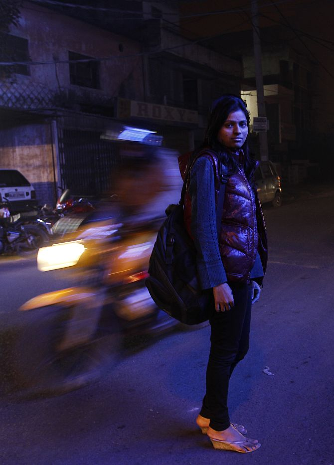 Sheetal, 23, who works at a night call centre, poses for a photograph outside her office in New Delhi