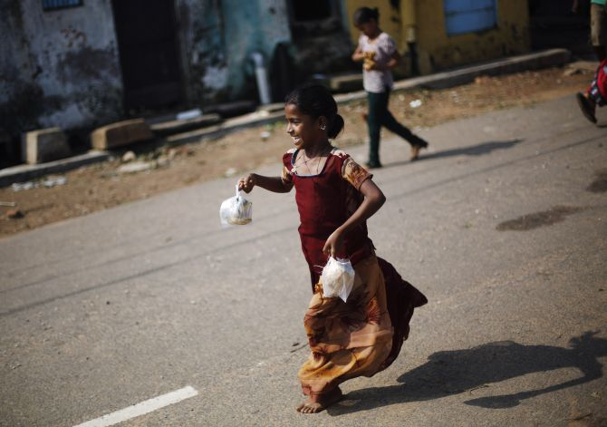 A girl runs home after receiving a free breakfast at the Cyclone Phailin-hit Gopalpur village, in Ganjam district of Odisha.