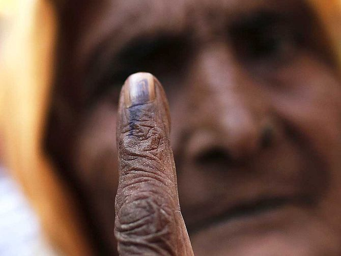 A woman shows her ink-marked finger after casting her vote.