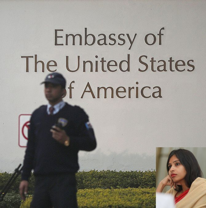 A US embassy security guard stands in front of the main gate of the embassy as the bulldozer (unseen) removes the security barriers, in New Delhi