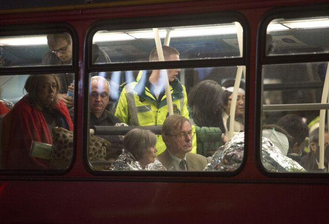 People receive medical attention on a bus after part of the ceiling at the Apollo Theatre on Shaftesbury Avenue collapsed in central London