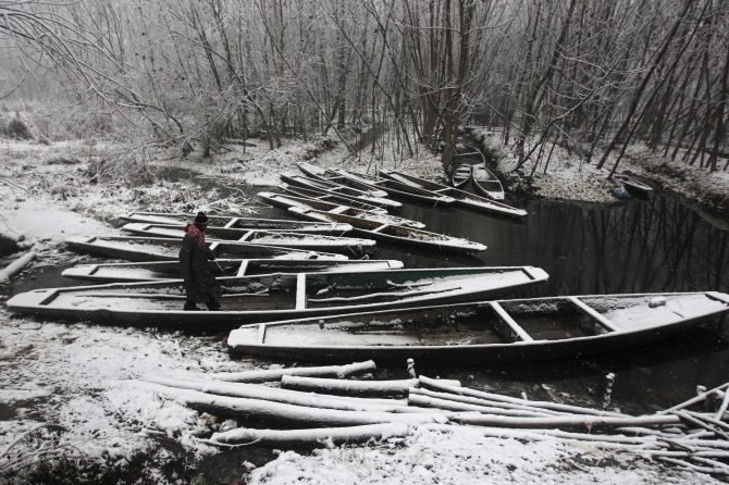 A Kashmiri man walks over snow covered parked boats in Srinagar