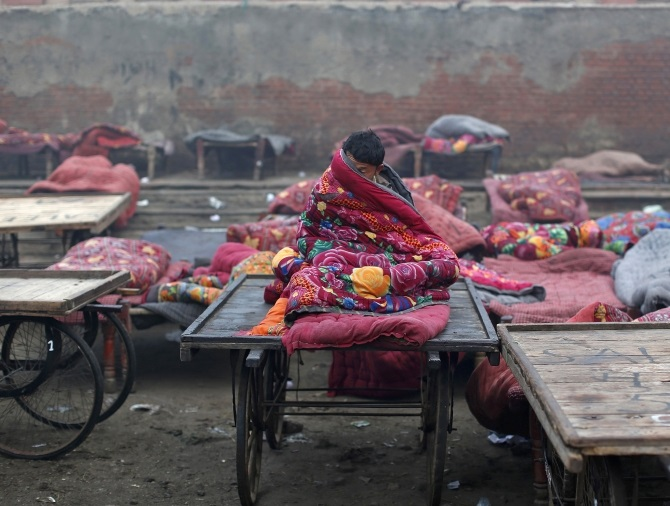 A migrant labourer sits under a quilt at an open space on a cold winter morning in the old quarters of Delhi